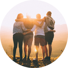 Four Travelers hugging at sunset