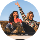 Two girls sitting on a top of a car